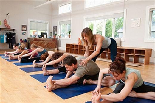 Класс йоги, учитель исправляет учеников.