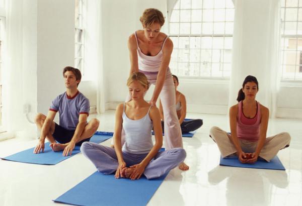 Учитель йоги исправляет учеников.
