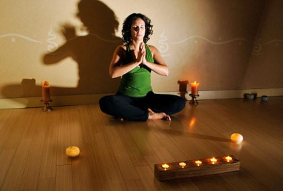 Девушка медитирует при свечах.